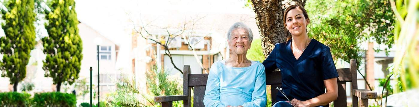 Elderly Patient and Female Nurse Smile at the Camera Outdoors