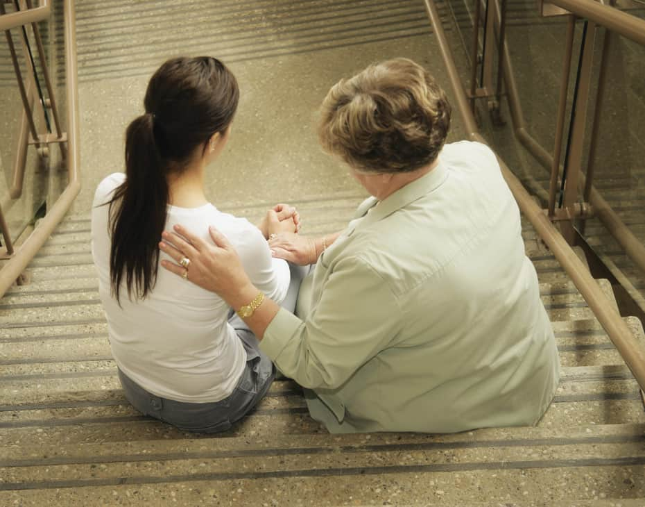 Elderly Woman Comforts a Young Woman on the Stairs