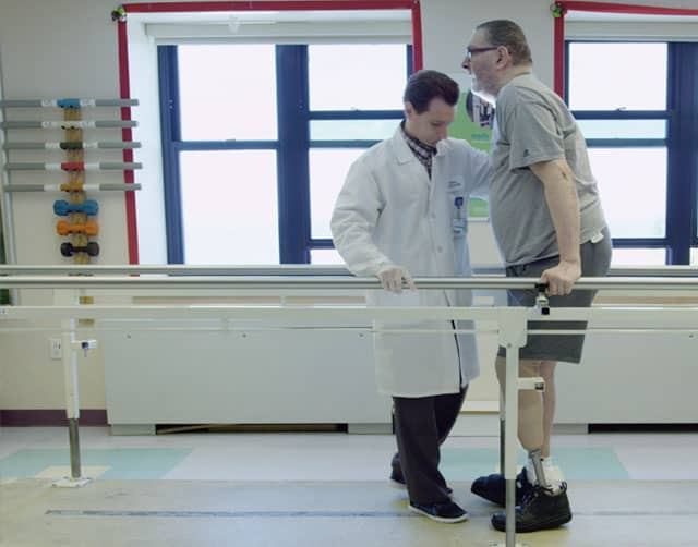 Doctor helping man with prosthetic leg