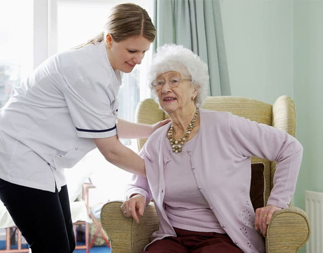 Nurse helping elderly woman get up from chair