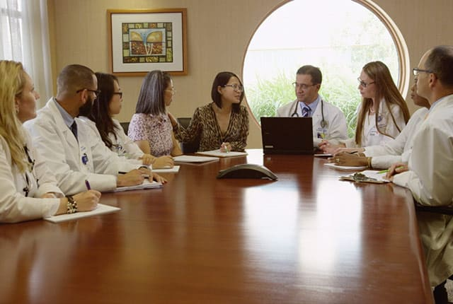 Women talking to doctors situated around a round table