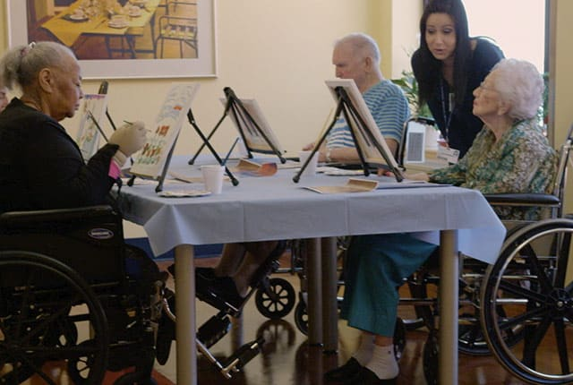 Four Seniors Painting on Easels at a Table with Staff Member