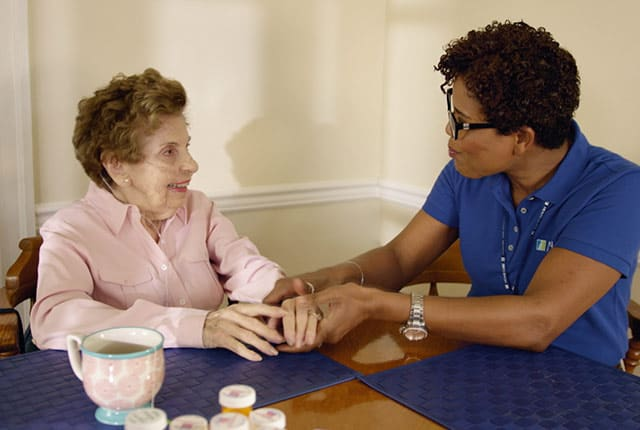 Nurse with elderly woman at a table