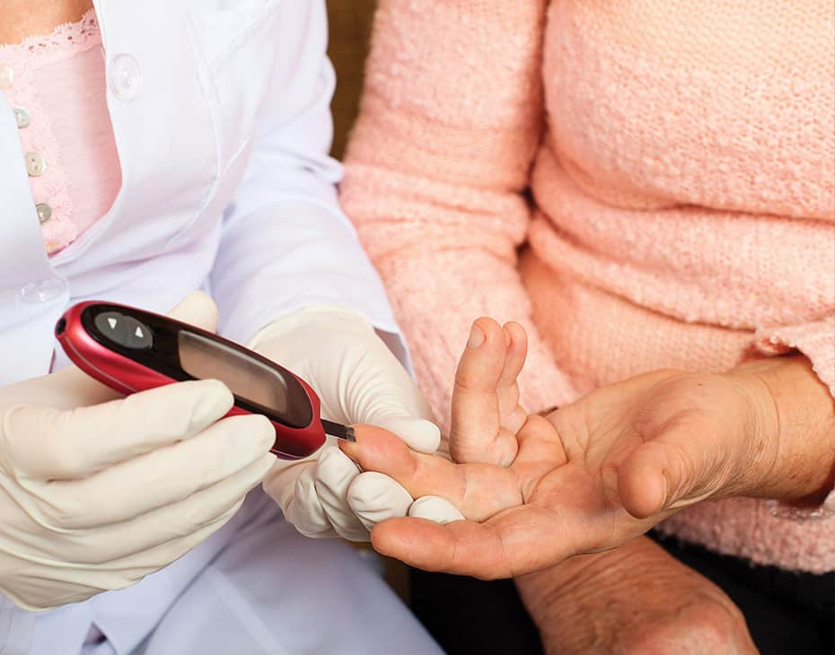 Nurse Checking Blood Sugar of Elderly Woman in Home