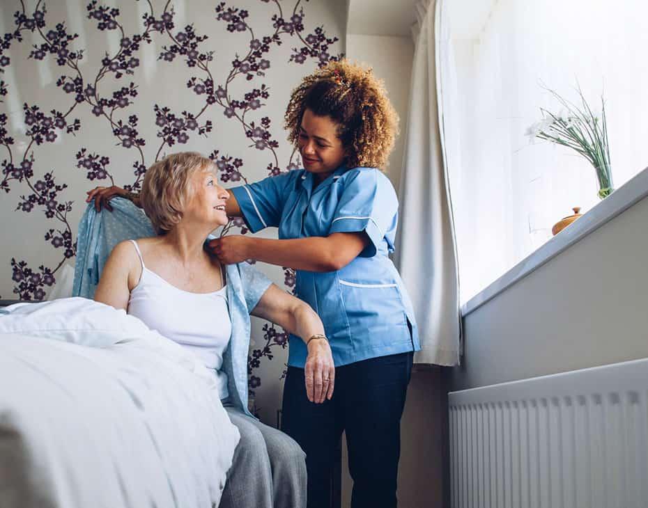 MJHS Nurse Assists Elderly Female Getting Dressed