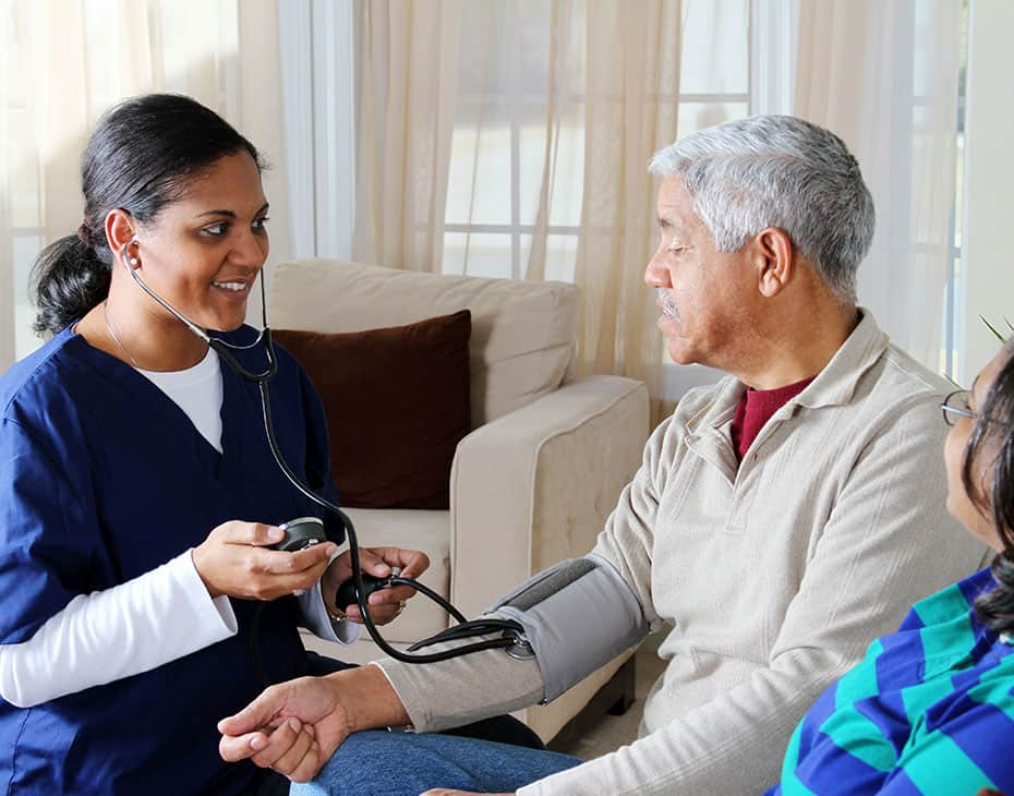 Female Home Caregiver Taking Senior Male's Blood Pressure with His Partner Nearby