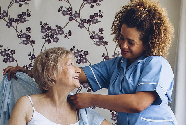 Nurse helping elderly woman with clothing
