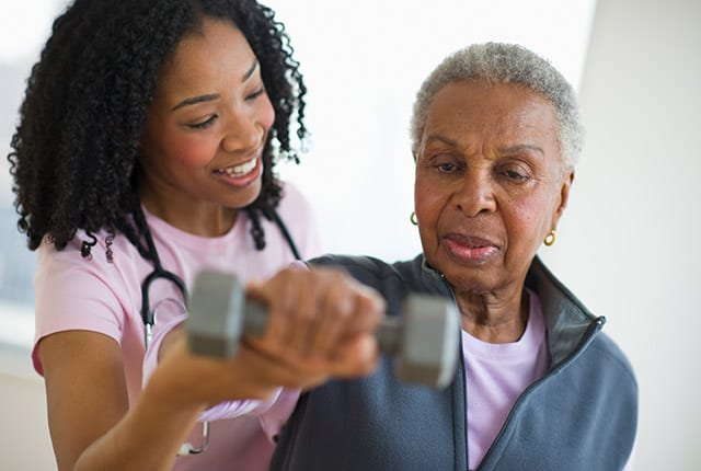 Nurse helping elderly woman with weights