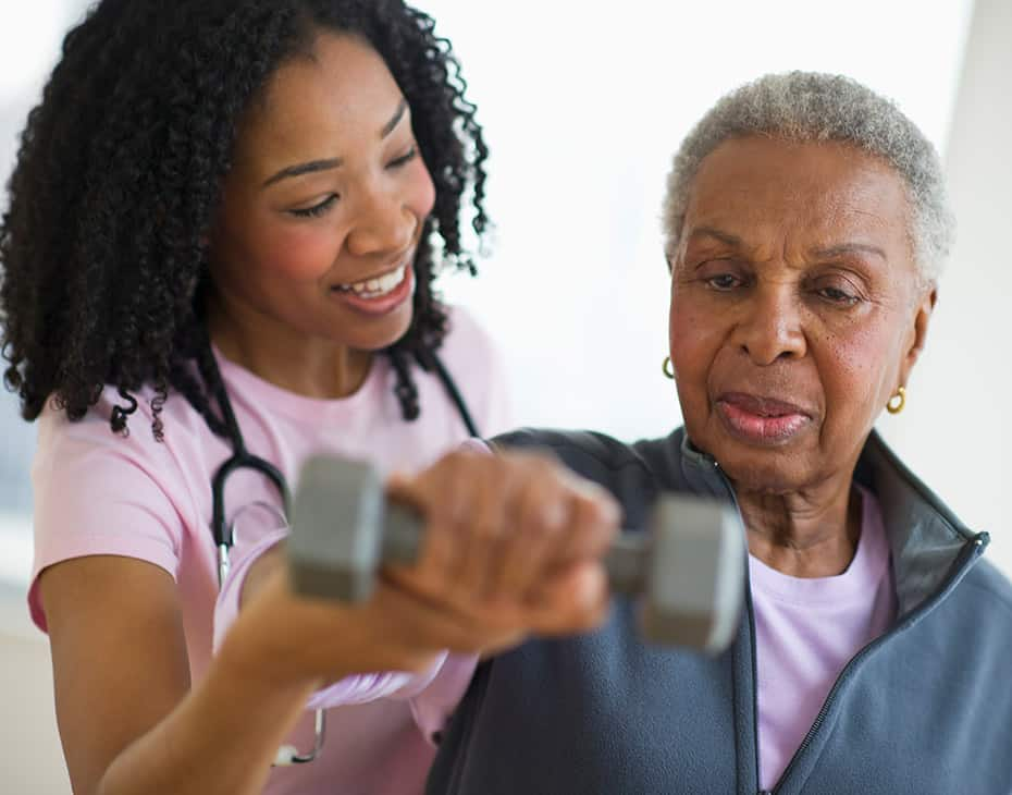 Smiling Nurse Helping Senior with Therapy by Using Dumbbell Exercise