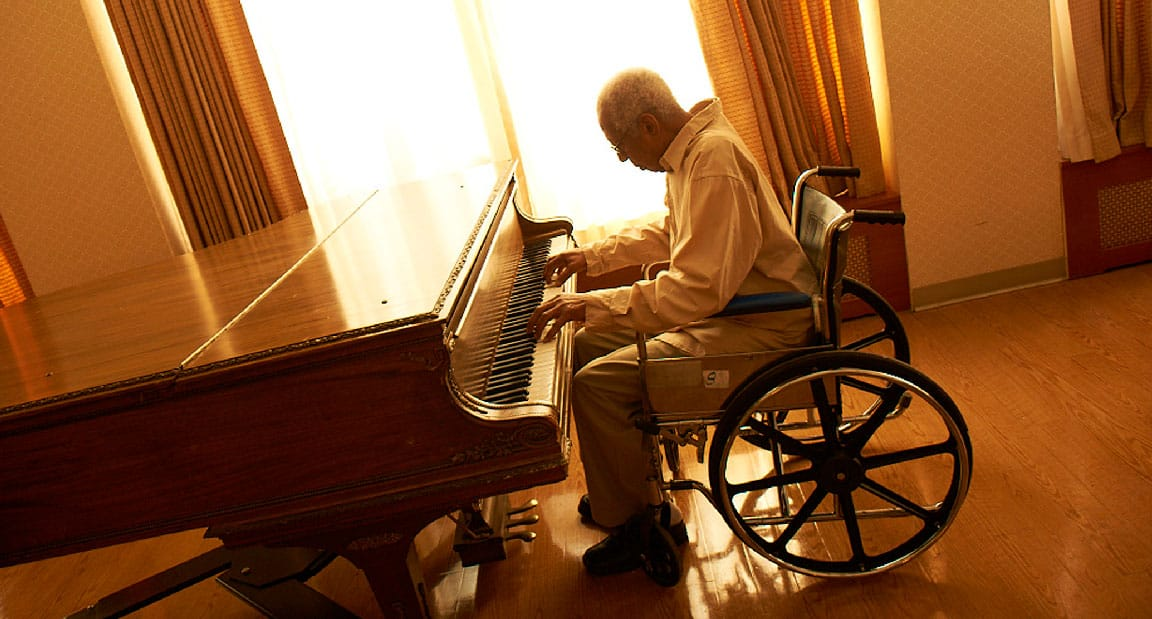 Long Term Elderly Man in a Wheelchair Plays the Piano