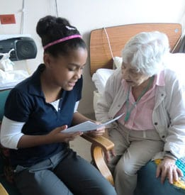 Young Female Reads to an Elderly Female Patient