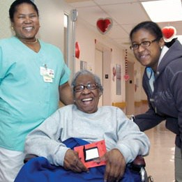 Patient in a Wheelchair Smiles with Nurse and Young Woman