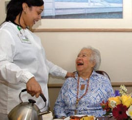 MJHS Caregiver Happily with Senior Resident Next to a Pot of Tea