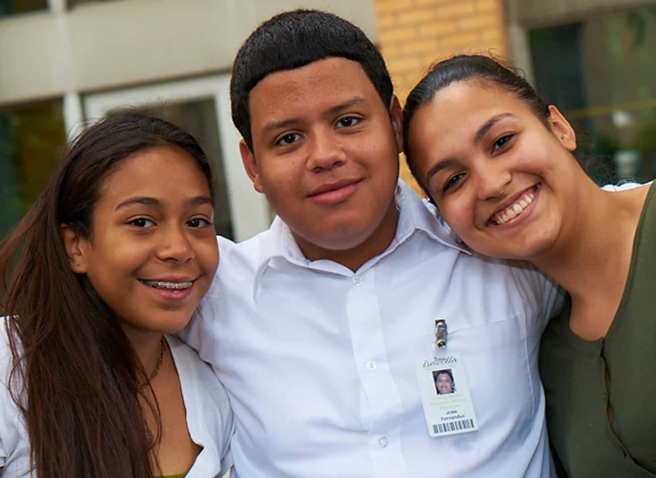 MJHS Volunteer Smiles with Two Younger Females