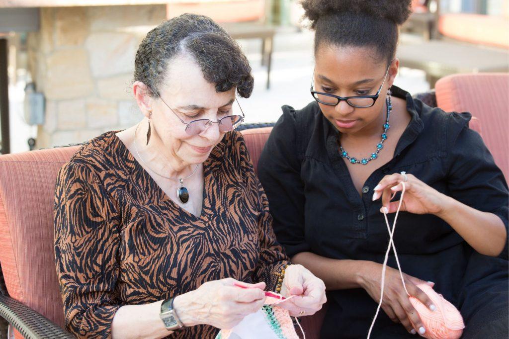 Grandma and Granddaughter talking and knitting together