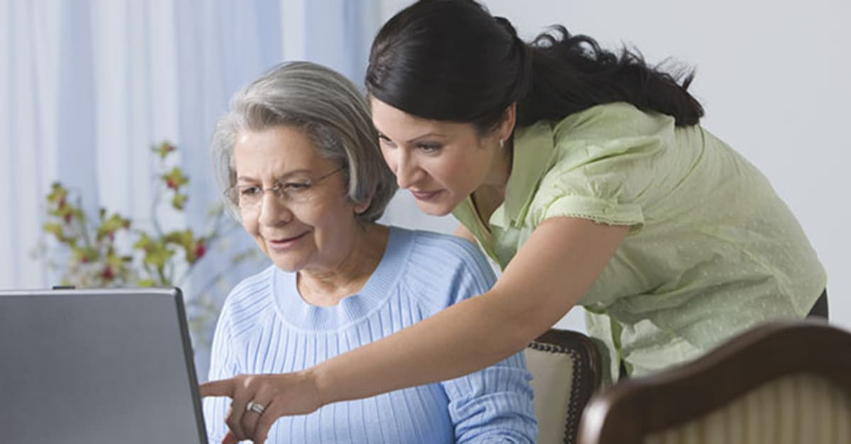 Caregiver And Loved One Looking at Laptop
